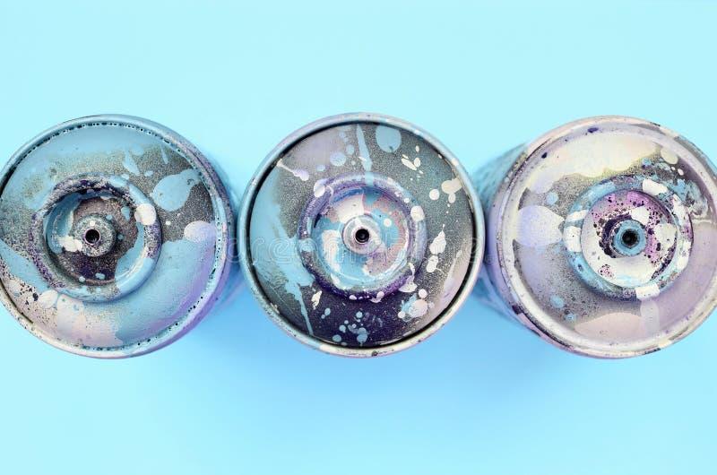 Μερικά χρησιμοποιημένα δοχεία ψεκασμού με τις μπλε σταλαγματιές χρωμάτων βρίσκονται στο υπόβαθρο σύστασης του μπλε εγγράφου χρώμα στοκ εικόνα με δικαίωμα ελεύθερης χρήσης