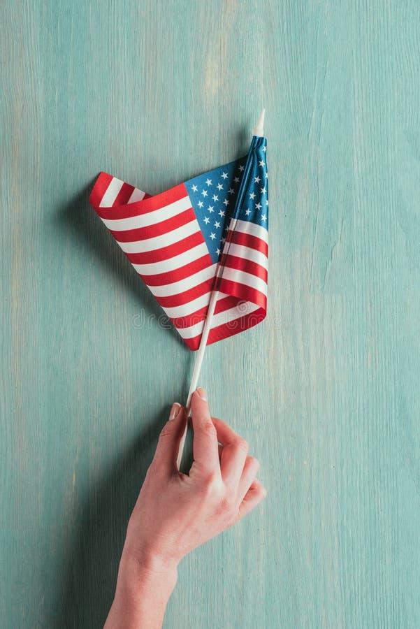 Μερική άποψη της αμερικανικής σημαίας εκμετάλλευσης γυναικών υπό εξέταση μπλε ξύλινο tabletop στοκ φωτογραφία
