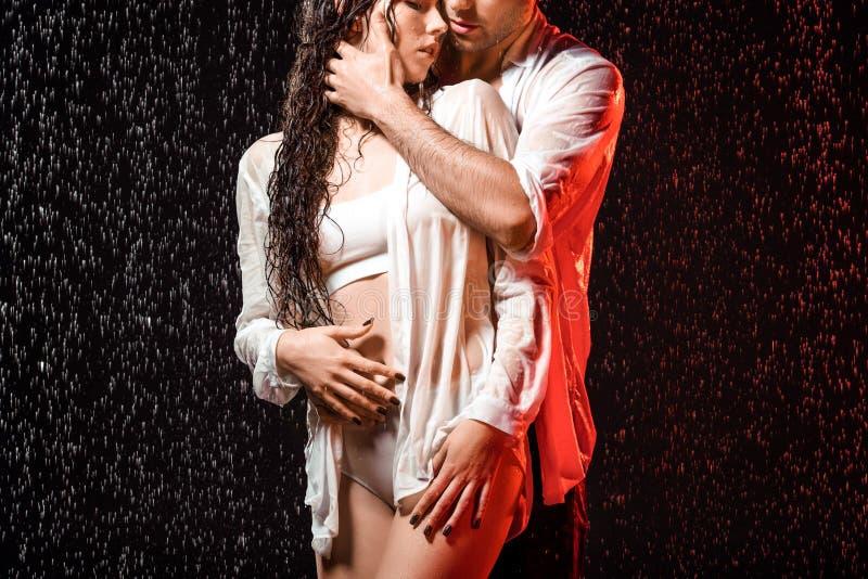μερική άποψη του προκλητικού ζεύγους στα άσπρα πουκάμισα που στέκονται κάτω από τη βροχή στοκ εικόνα