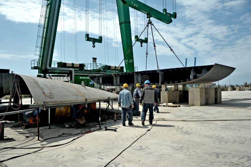 Μερικοί εργαζόμενοι που εργάζονται σε ένα ναυπηγείο μεταξύ των μεγάλων γερανών για την κατασκευή ενός μέγα γιοτ στοκ φωτογραφίες