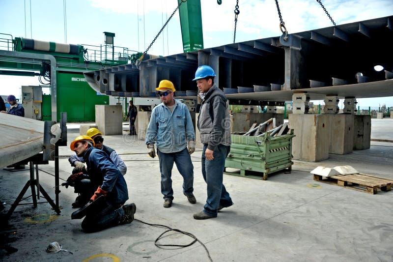Μερικοί εργαζόμενοι που εργάζονται σε ένα ναυπηγείο μεταξύ των μεγάλων γερανών για την κατασκευή ενός μέγα γιοτ στοκ φωτογραφία με δικαίωμα ελεύθερης χρήσης