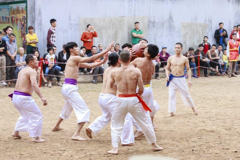Μερικοί νεαροί άνδρες παίζουν με την ξύλινη σφαίρα στο σεληνιακό νέο έτος φεστιβάλ στο Ανόι, Βιετνάμ στις 27 Ιανουαρίου 2016 στοκ φωτογραφία