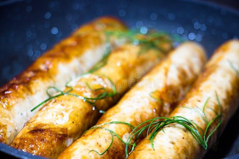 Μερικοί τηγάνισαν, φρέσκος και τα ευώδη λουκάνικα, βρίσκονται σε ένα μαύρα τηγανίζοντας τηγάνι και τηγανητά στοκ εικόνα