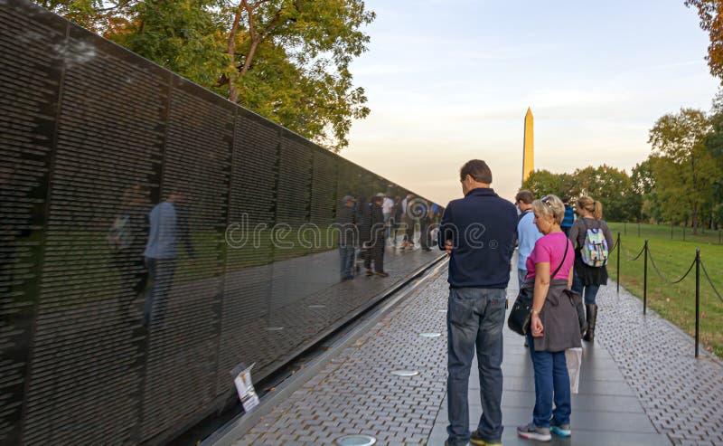 μερικοί τουρίστες που συλλογίζονται τον αναμνηστικό τοίχο του Βιετνάμ με το μνημείο του George Washington στο υπόβαθρο στοκ φωτογραφία με δικαίωμα ελεύθερης χρήσης