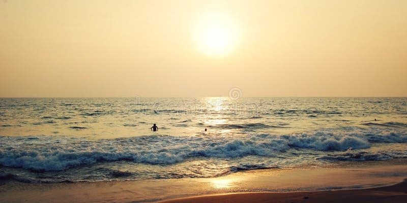Μερικοί τουρίστες στην τροπική ωκεάνια παραλία - αναδρομική επίδραση Ηλιοβασίλεμα σε Varkala στοκ φωτογραφία με δικαίωμα ελεύθερης χρήσης