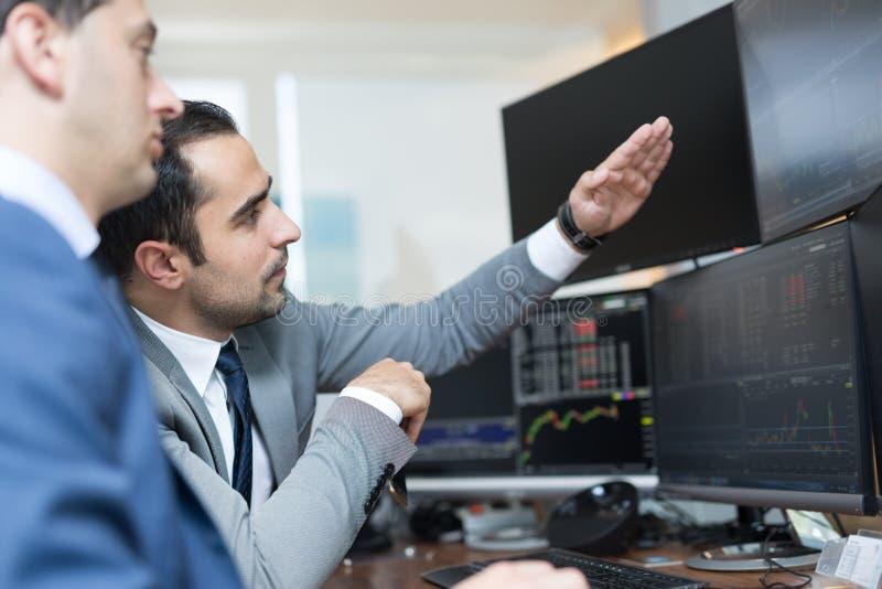 Μεσίτες αποθεμάτων που εξετάζουν τις οθόνες υπολογιστή, που κάνουν εμπόριο on-line στοκ εικόνα με δικαίωμα ελεύθερης χρήσης