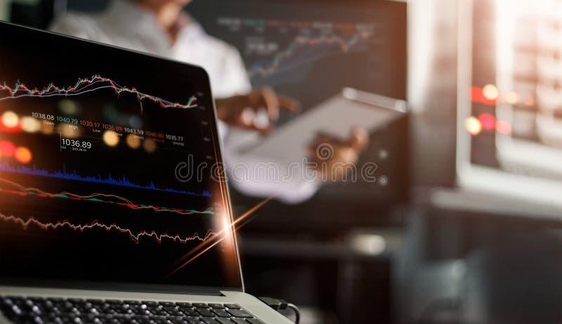 Μεσίτες με το lap-top, χρηματιστήριο στοιχείων στην οθόνη στοκ φωτογραφία