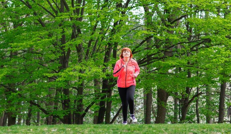 Μεσαίωνας womn που φορά sportswear και που τρέχει στο δάσος στοκ φωτογραφία με δικαίωμα ελεύθερης χρήσης