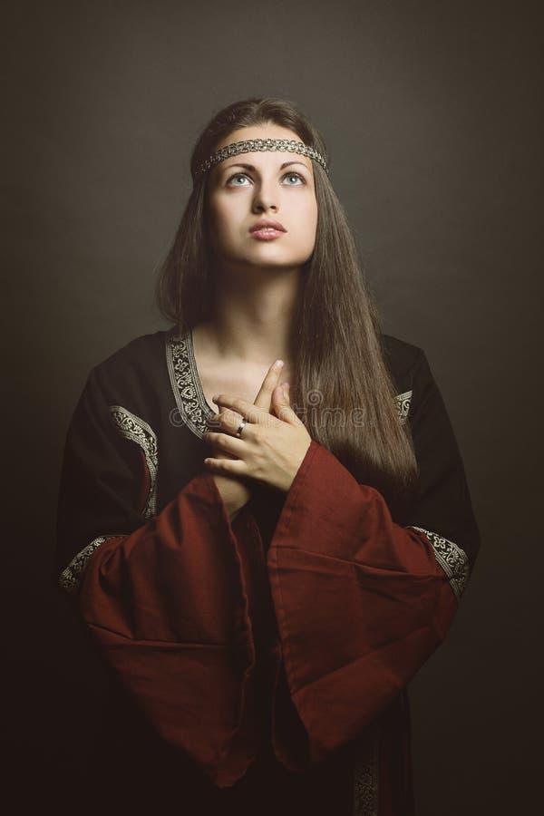 Μεσαιωνική γυναίκα με τα μάτια στον ουρανό στοκ φωτογραφία