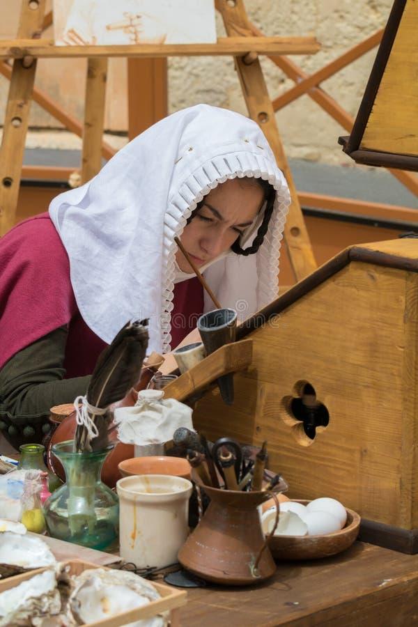 Μεσαιωνικός γραφέας που ασκεί την παραδοσιακή καλλιγραφία γραψίματος φωτισμού στοκ φωτογραφία με δικαίωμα ελεύθερης χρήσης