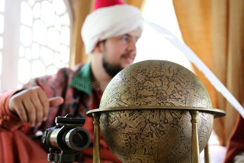 Μεσαιωνικός επιστήμονας της οθωμανικής αυτοκρατορίας με μια αρχαία σφαίρα και ένα τηλεσκόπιο στοκ εικόνα με δικαίωμα ελεύθερης χρήσης