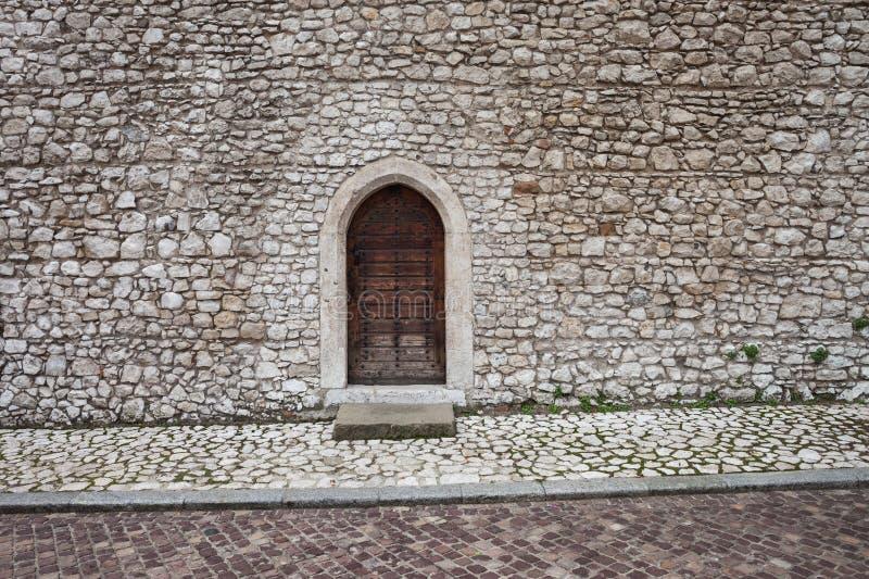 Μεσαιωνικός πέτρινος τοίχος του Castle με την πόρτα στοκ εικόνες