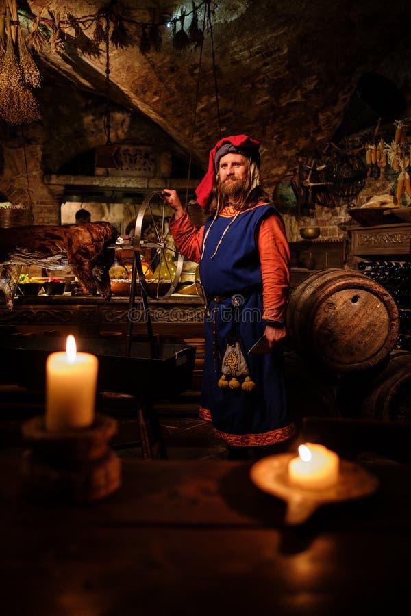 Μεσαιωνικό άτομο που κάνει τον ψημένο χοίρο στο ράφι στην αρχαία κουζίνα κάστρων στοκ φωτογραφία με δικαίωμα ελεύθερης χρήσης