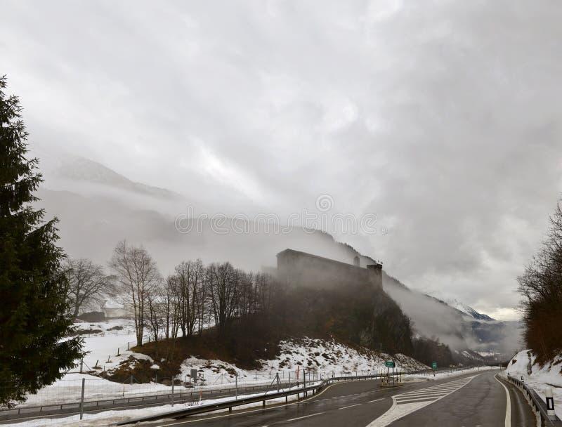Μεσαιωνικό κάστρο μεταξύ των χαμηλών χειμερινών σύννεφων, Mesocco, Ελβετία στοκ εικόνες