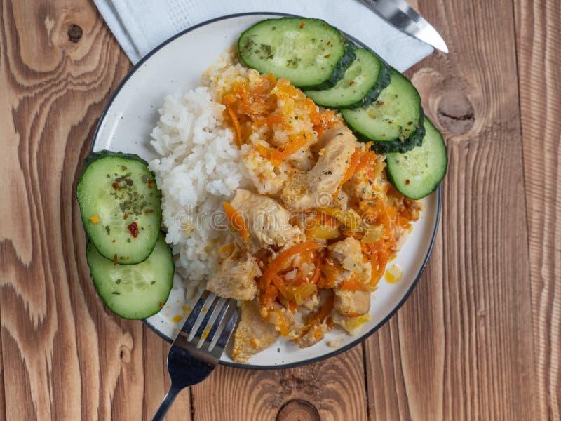 Μεσημεριανό γεύμα του κοτόπουλου και του ρυζιού σε ένα πιάτο σε μια πετσέτα λινού, φέτες του φρέσκου αγγουριού, καρότα, δίκρανο σ στοκ εικόνες