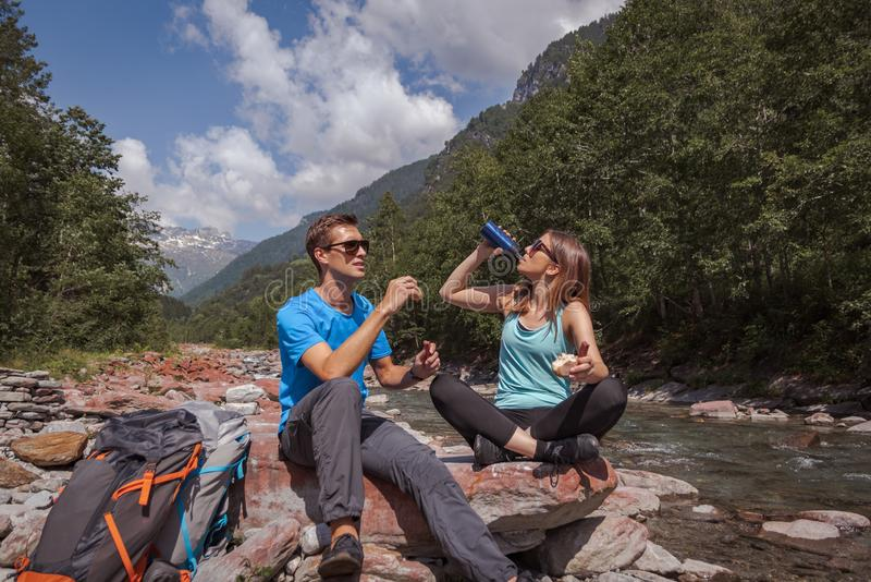 Μεσημεριανό διάλειμμα ζευγών Backpackers με το landjaeger και το ψωμί σε έναν ποταμό στοκ φωτογραφία με δικαίωμα ελεύθερης χρήσης