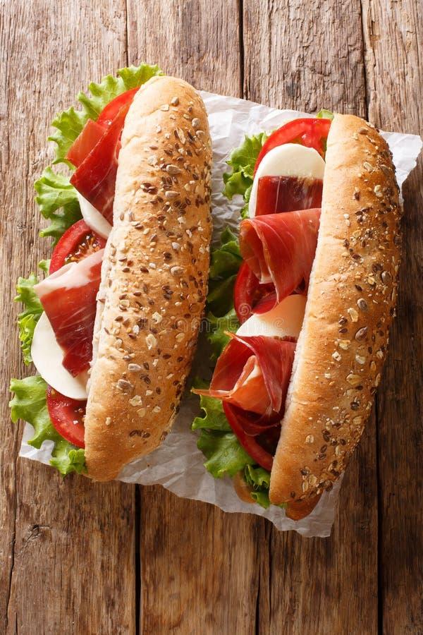 Μεσογειακά σάντουιτς με το jamon, το τυρί μοτσαρελών, τις ντομάτες και την κινηματογράφηση σε πρώτο πλάνο μαρουλιού φύλλων Κάθετη στοκ εικόνα με δικαίωμα ελεύθερης χρήσης
