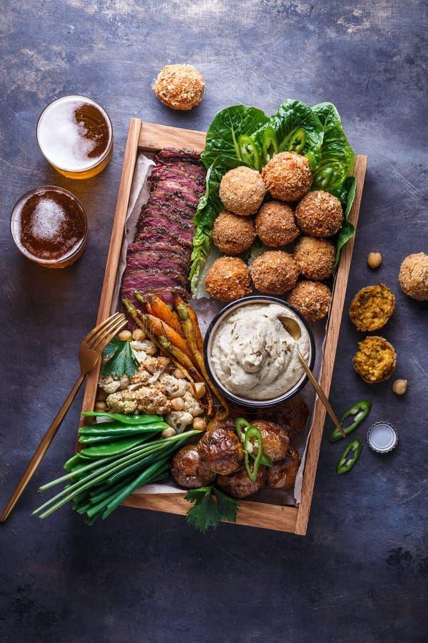 Μεσο-Ανατολικά τρόφιμα κομμάτων: falafel, babaghanoush, πατάτες, βόειο κρέας, πράσινα veggies στοκ φωτογραφία