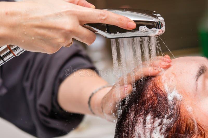 Μετά από να βάψει την τρίχα, ο κομμωτής πλένει την τρίχα και τα πλυσίματα κοριτσιών ` s από το σαμπουάν στοκ εικόνες