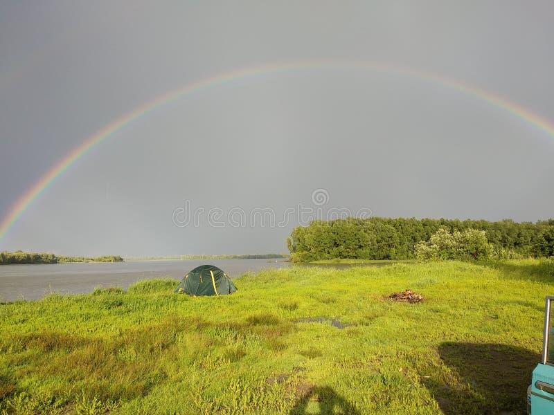 Μετά από τη βροχή, τεντώματα φωτεινά ουράνιων τόξων πέρα από τον ποταμό Ob στοκ εικόνες