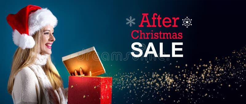Μετά από το μήνυμα πώλησης Χριστουγέννων με τη γυναίκα που ανοίγει ένα κιβώτιο δώρων στοκ φωτογραφία