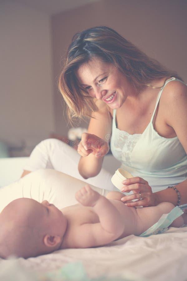 Μεταβαλλόμενη πάνα μητέρων αυτή λίγο μωρό στο κρεβάτι Χρησιμοποίηση μητέρων στοκ φωτογραφία με δικαίωμα ελεύθερης χρήσης