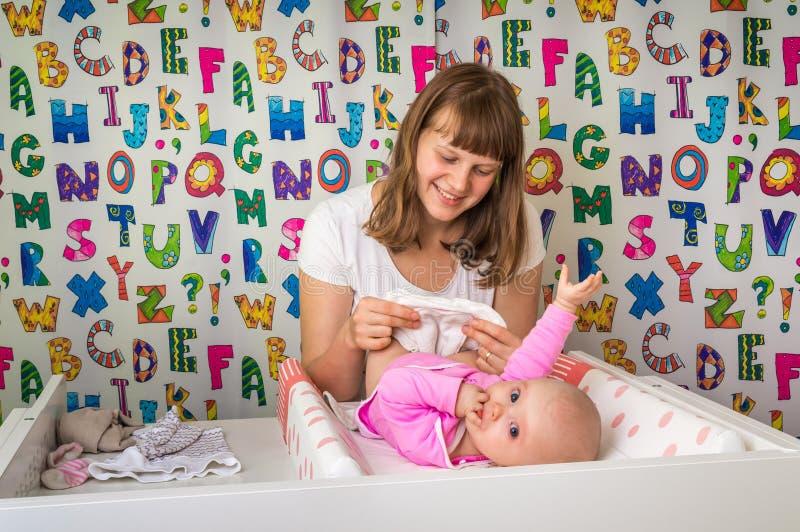 Μεταβαλλόμενη πάνα μητέρων σε την λίγο μωρό στο δωμάτιο παιδιών στοκ εικόνες