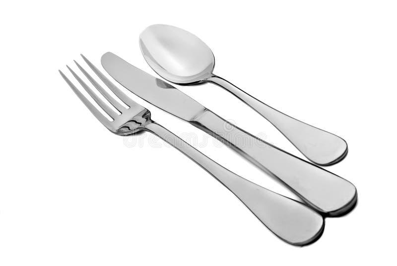 Μετακινήστε με το κουτάλι το δίκρανο και το μαχαίρι σε μια άσπρη ανασκόπηση στοκ φωτογραφίες