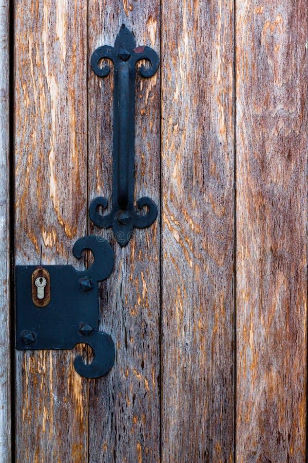 Μεταλλική λαβή πορτών σε μια ξύλινη πόρτα στοκ φωτογραφίες