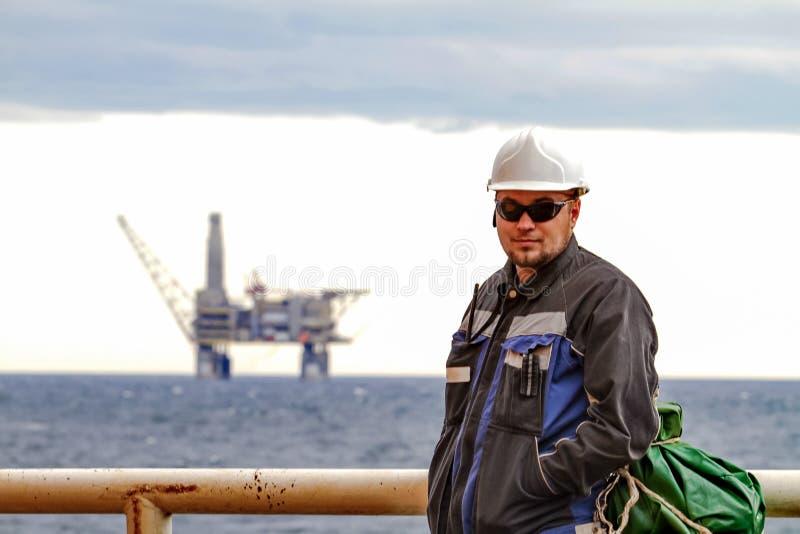 Μετατόπιση Oilman - εργαζόμενοι στο κατάστρωμα του πλοίου στις παράκτιες κατόψεις ραφιών πετρελαίου υποβάθρου Εργασία για τον τρό στοκ εικόνες