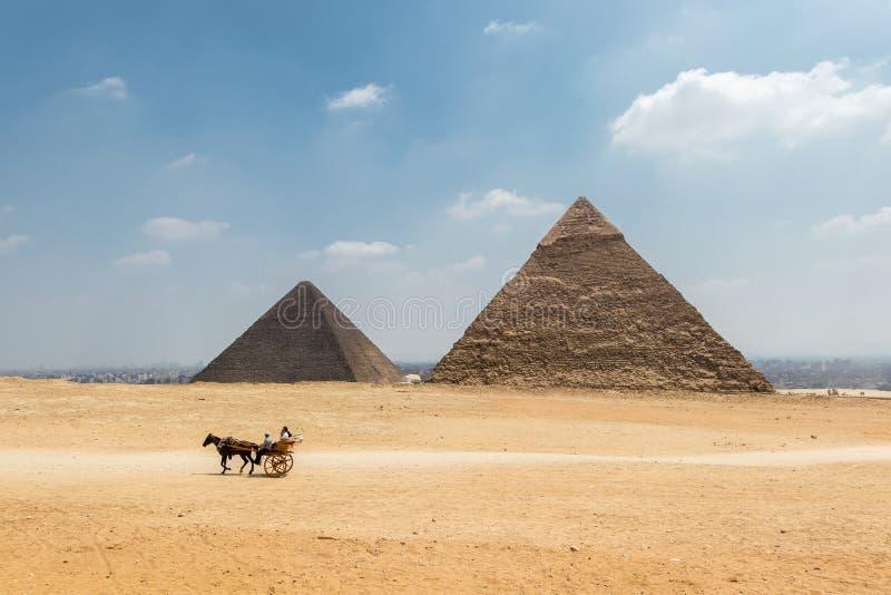 Μεταφορά αλόγων με τους τουρίστες μπροστά από την πυραμίδα στοκ φωτογραφία με δικαίωμα ελεύθερης χρήσης