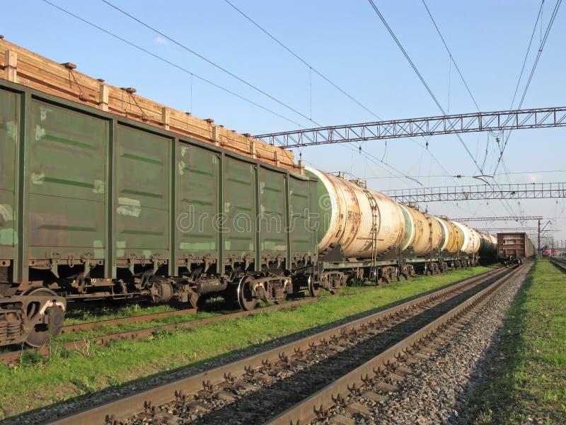 Μεταφορά φορτίου με το τραίνο, δεξαμενές με τα καύσιμα, εμπορευματοκιβώτιο με την ξυλεία στοκ φωτογραφίες