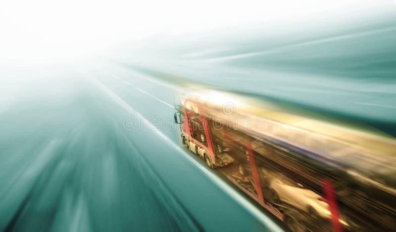 Μεταφορέας αυτοκινήτων στη θαμπάδα οδικών κινήσεων ασφάλτου στοκ φωτογραφία