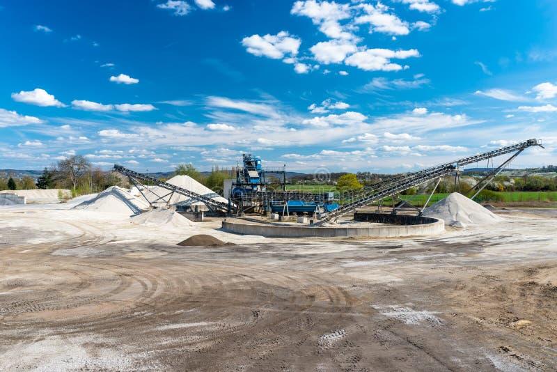 Μεταφορέας πέρα από τους σωρούς του αμμοχάλικου στο μπλε ουρανό σε μια βιομηχανική τσιμεντοβιομηχανία στοκ φωτογραφίες με δικαίωμα ελεύθερης χρήσης