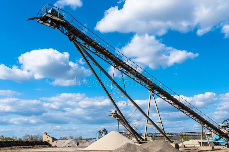Μεταφορέας πέρα από τους σωρούς του αμμοχάλικου στο μπλε ουρανό σε μια βιομηχανική τσιμεντοβιομηχανία στοκ φωτογραφία με δικαίωμα ελεύθερης χρήσης