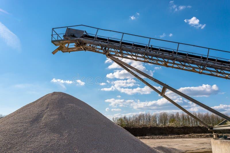 Μεταφορέας πέρα από τους σωρούς του αμμοχάλικου στο μπλε ουρανό σε μια βιομηχανική τσιμεντοβιομηχανία στοκ εικόνες με δικαίωμα ελεύθερης χρήσης