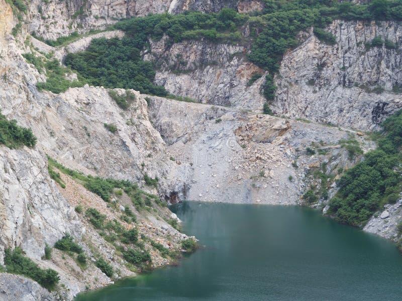 Μεταλλεία ανοικτών κοιλωμάτων γρανίτη με τη γαλαζοπράσινη λίμνη στοκ φωτογραφία