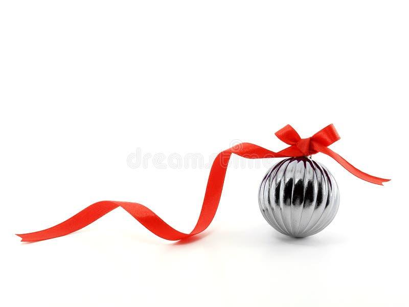 Μεταλλική σφαίρα Χριστουγέννων με το κόκκινο τόξο κορδελλών στοκ εικόνα