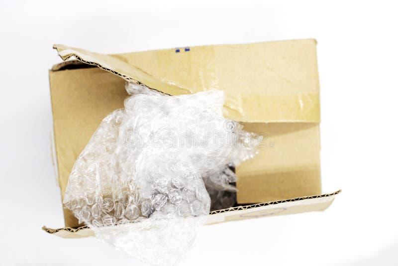 Μετα κιβώτιο δεμάτων με το πλαστικό συσκευασίας στο άσπρο υπόβαθρο, τοπ φωτογραφία άποψης διαδικασίας Unboxing Άνοιγμα κιβωτίων χ στοκ εικόνες