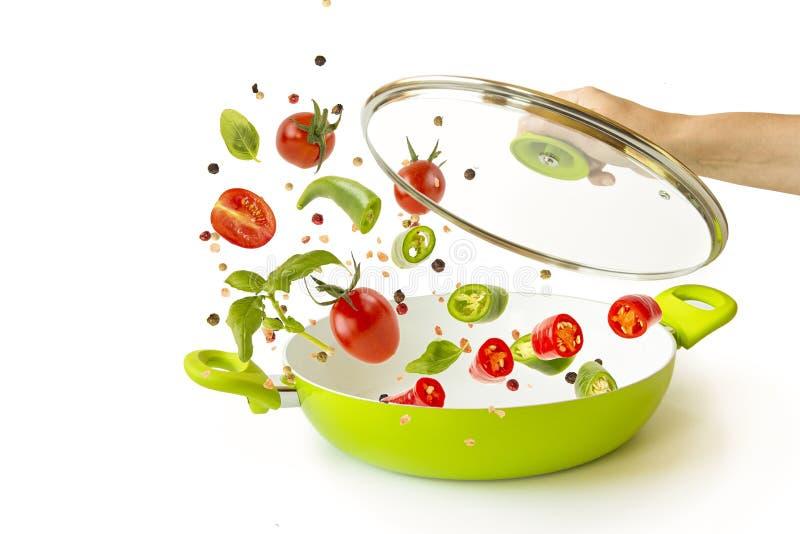 Μετεωρισμός Ρίχνουν τα ψάρια και τα λαχανικά με τα καρυκεύματα σε ένα πράσινο τηγάνι στοιχεία στο άσπρο υπόβαθρο Πετώντας τρόφιμα στοκ εικόνα με δικαίωμα ελεύθερης χρήσης