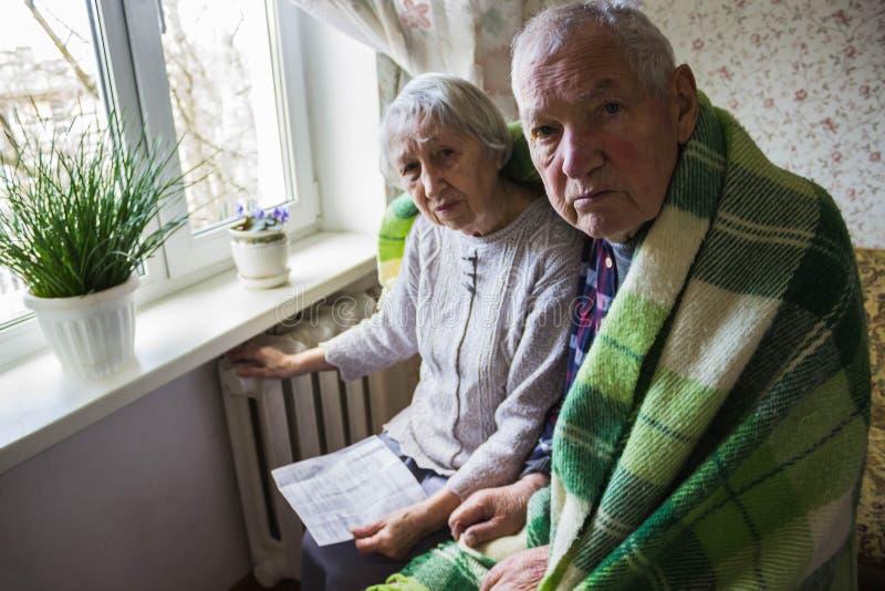 Μετρητά εκμετάλλευσης γυναικών μπροστά από τη θέρμανση του θερμαντικού σώματος Πληρωμή για τη θέρμανση το χειμώνα Εκλεκτική εστία στοκ εικόνες