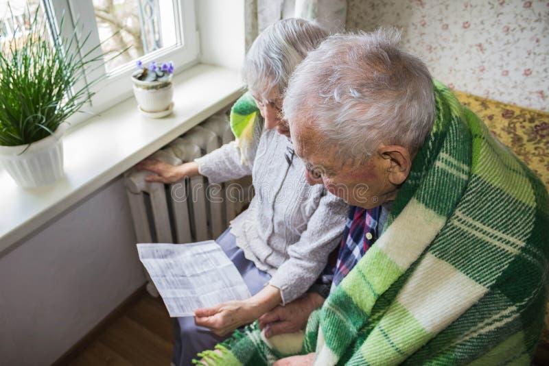 Μετρητά εκμετάλλευσης γυναικών μπροστά από τη θέρμανση του θερμαντικού σώματος Πληρωμή για τη θέρμανση το χειμώνα Εκλεκτική εστία στοκ φωτογραφία με δικαίωμα ελεύθερης χρήσης