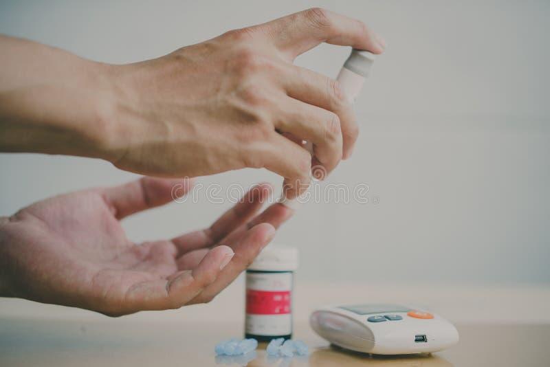 Μετρητής γλυκόζης αίματος Κλείστε επάνω των χεριών γυναικών χρησιμοποιώντας το νυστέρι στοκ φωτογραφία