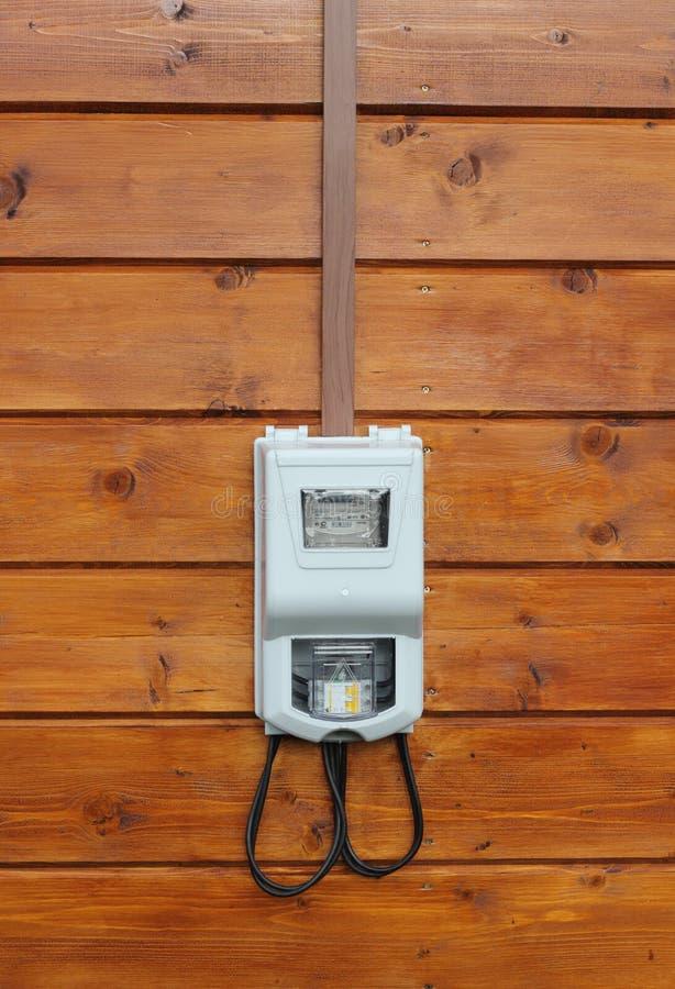 Μετρητής παροχής ηλεκτρισμού στην ξύλινη μπροστινή άποψη τοίχων στοκ εικόνες
