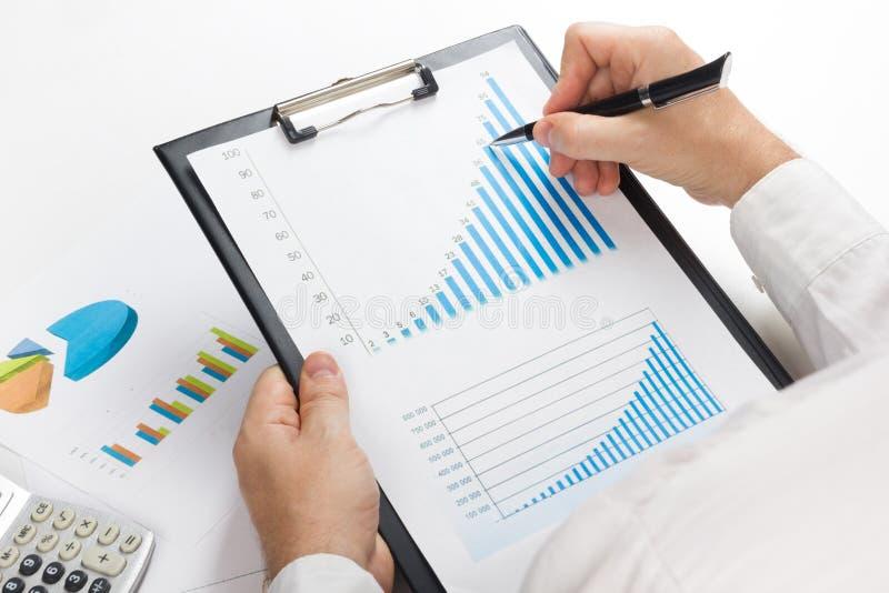 Μετρώντας απώλειες και κέρδος επιχειρηματιών που λειτουργούν με τις στατιστικές, ανάλυση οικονομική τα αποτελέσματα για το άσπρο  στοκ φωτογραφία