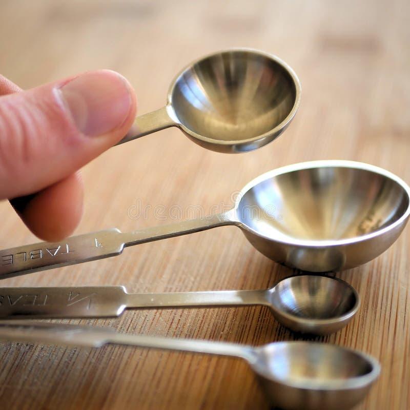 Μετρώντας κουτάλια μετάλλων στον ξύλινο τέμνοντα πίνακα σιταριού στην κουζίνα στοκ εικόνες