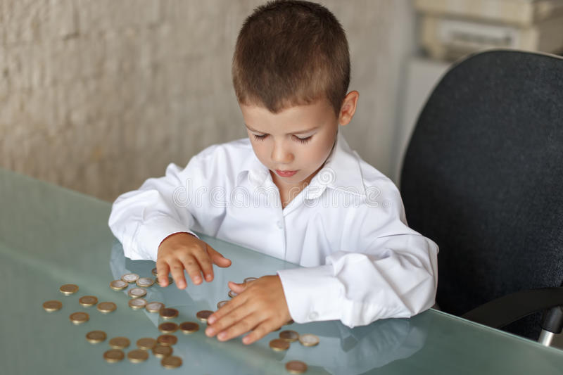 Μετρώντας νομίσματα λίγων καυκάσια αγοριών διευθυντών στο γραφείο στοκ φωτογραφία με δικαίωμα ελεύθερης χρήσης