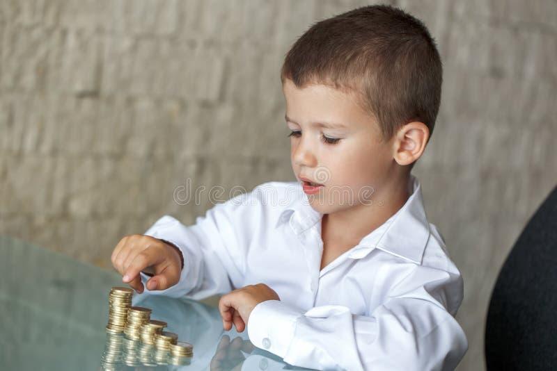 Μετρώντας νομίσματα μικρών παιδιών στο γραφείο γυαλιού στοκ εικόνα