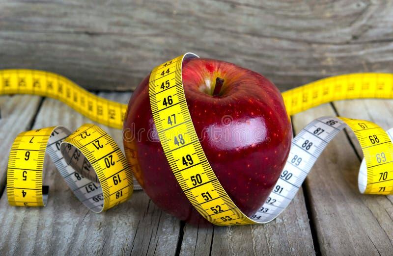 Μετρώντας την ταινία που τυλίγεται γύρω από μια απώλεια βάρους μήλων στοκ φωτογραφία