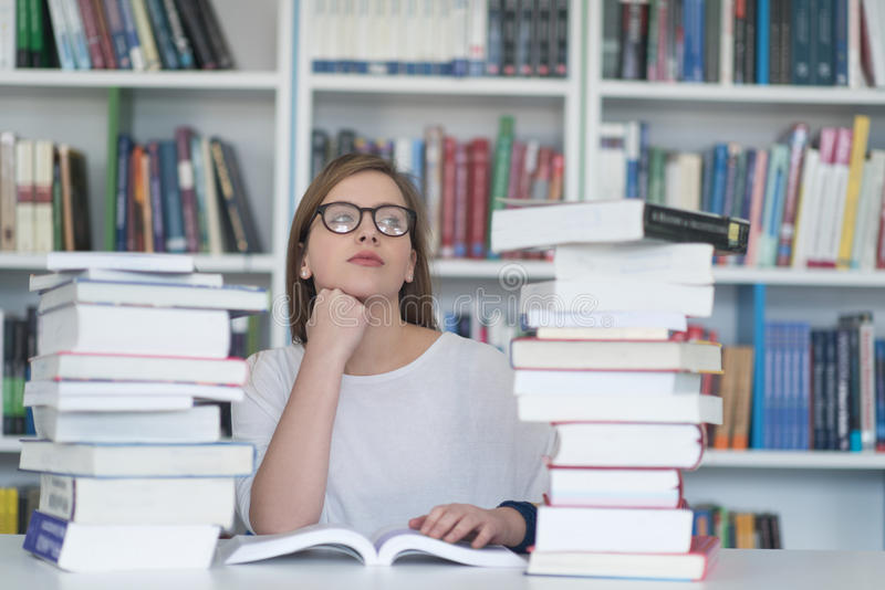 Μελέτη γυναικών σπουδαστών στη βιβλιοθήκη, χρησιμοποιώντας την ταμπλέτα και ψάχνοντας για στοκ φωτογραφία με δικαίωμα ελεύθερης χρήσης